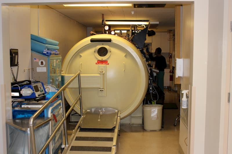 ED member standing next to a hyperbaric chamber